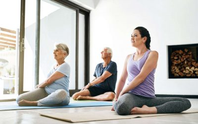 Shot of an instructor guiding a senior couple in a yoga class